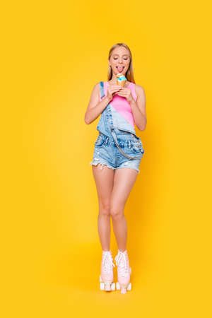 Fullbody vertical portrait of hungry slim girl in jeans overall on roller skates licking ice-cream with tongue out isolated on vivid yellow background Stock Photo