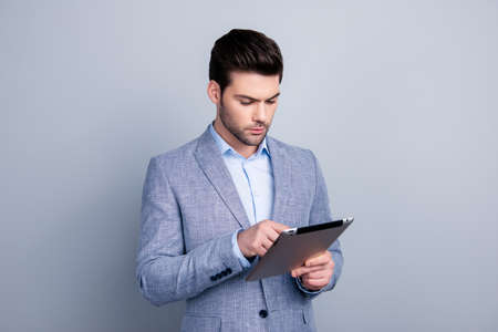 Portrait of smart attractive manager in jacket and shirt using wifi internet on tablet, chatting with friends, checking email, isolated on grey background