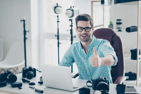 Portrait of positive attractive man with bristle in shirt sitting at desk with camera tools in service center using computer showing thumb up to the camera
