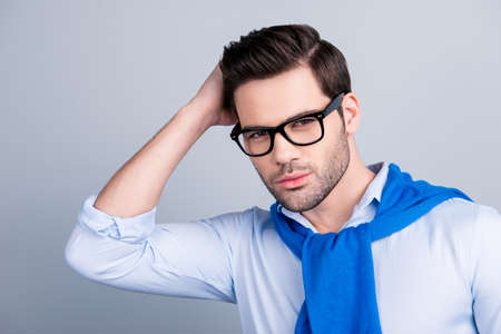 Stunning cool macho holding hand on his hair, correcting his hairstyle, having tied blue sweater around the neck, looking at camera, isolated on grey background Stok Fotoğraf