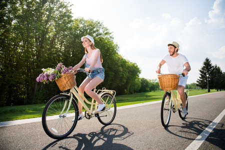 Movement active activity daydream serenity delight concept. Cheerful positive couple riding retro bikes with basket and bouquet in park. He vs she together forever enjoying sunny beautiful day