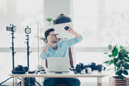 Portrait of professional expert sitting at desktop in camera service, looking carefully at lens holding hand on eyelet of glasses on his face, having a lot of equipments on the table and strobe light