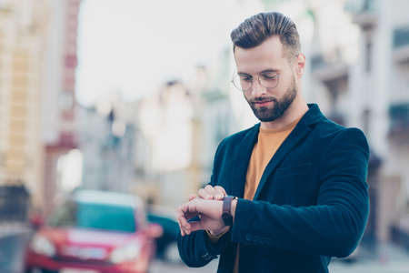 Portrait of smart responsible man with modern hairdo looking at watch on wrist over blurred street background hurry up for meeting. Management employment job concept Stock Photo
