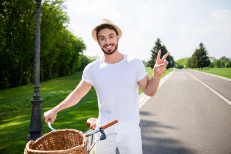 Portrait of cheerful positive attractive man in white outfit having bike gesturing two fingers v-sign with hand looking at camera. Harmony daydream serenity concept