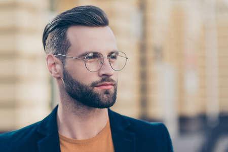 Ritratto con copia-spazio di intelligente uomo premuroso con moderna pettinatura barba che guarda lontano isolato su sfondo sfocato. Concetto di autorità della società persona persona Archivio Fotografico