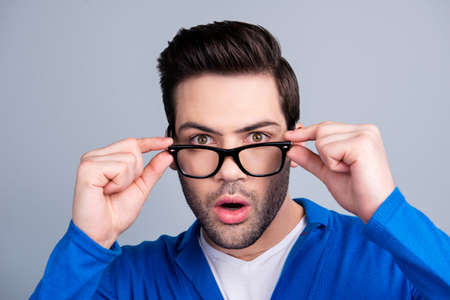 Portrait of amazed man looking out glasses, holding eyelets with two hands, having open mouth, isolated on grey background, dressed in blue pullover 写真素材