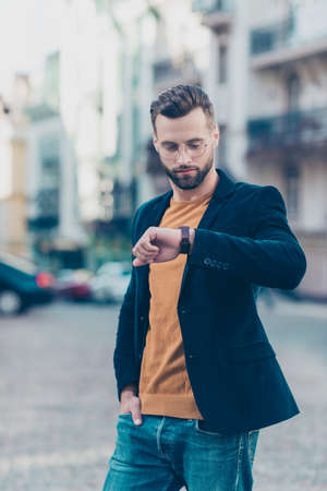 Vertical portrait of attractive responsible man waiting for lover looking at watch on wrist holding hand in pocket of jeans standing over blurred street background Stock Photo