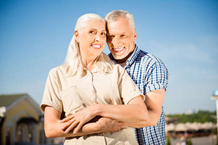 Portrait of cheerful positive couple in casual outfits embracing over blue sky looking at camera. Idyllic harmony delight concept Stock Photo