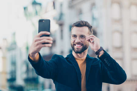 Portrait of cheerful joyful man in eyewear jacket holding eyelet of glasses on face shooting selfie on front camera of smart phone isolated on blurred background. Vacation weekend holiday concept