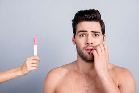 Girls hand showing result of pregnancy test to boyfriend, attractive guy hold hand near mouth in utter confusion, he is not ready become a father, isolated on grey background