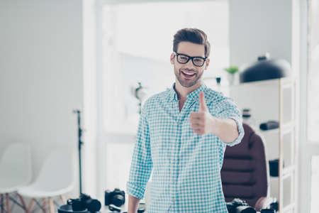 Porträt eines positiven fröhlichen Kerls im Hemd mit Stoppeln und moderner Frisur, der im Fotostudio steht, lacht, Daumen hoch zur Kamera gestikuliert