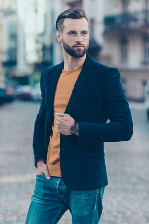 Vertical portrait of attractive caucasian man with modern hairdo looking away with dreamy expression standing over blurred street background. High fashion glamour trend concept