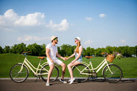 Full length size bode portrait of lovely romantic couple after riding on bikes talking speaking holding hands enjoying time together on holidays over beautiful lanscape