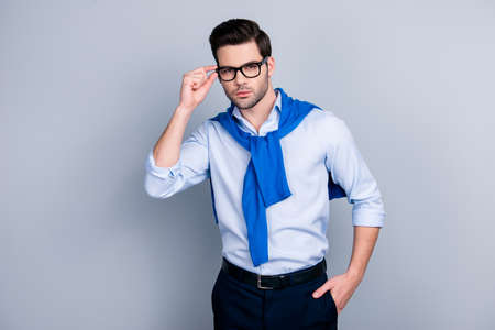 Portrait of cool stunning guy with tied blue sweater around neck, holding hand in pocket of pants and eyelet of glasses on his face, posing for camera over grey background