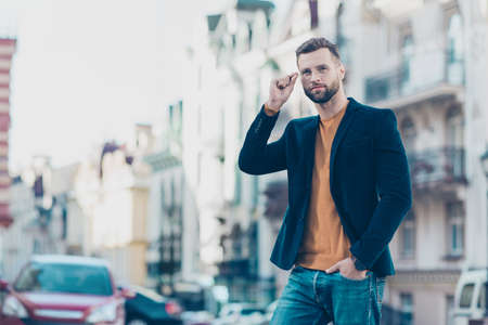 Portrait of manly stunning man in jacket looking away holding eyelet of glasses on face walking on street. Rest relax break leisure vacation weekend holiday concept Stock Photo