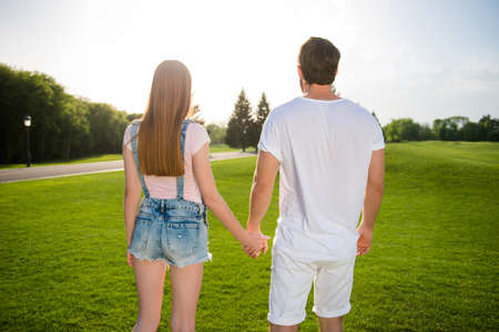 He vs she together forever! Portrait of loving beautiful couple in casual outfit jeans overall holidng hands while walking in park outside outdoor Stock Photo