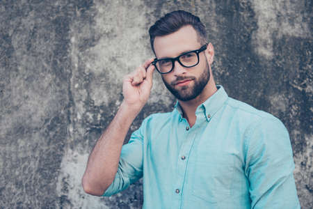 Portrait of clever modern guy holding eyelet of glasses on face looking at camera wearing classic blue shirt isolated over stone grey background. Health eye care examine concept Stock Photo