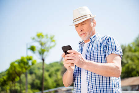 Low angle view of attractive business man over blurred street background holding smart phone in hands using 4G internet chatting with friends searching contact. Electronic wireless device concept