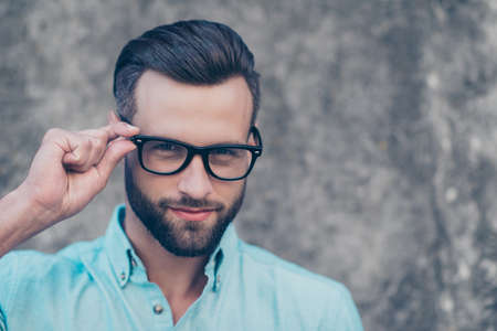 Head shot portrait with copyspace of stunning cool man holding eyelet of glasses on face looking at camera isolated on grey background. Eye care problem treatment concept Stock Photo