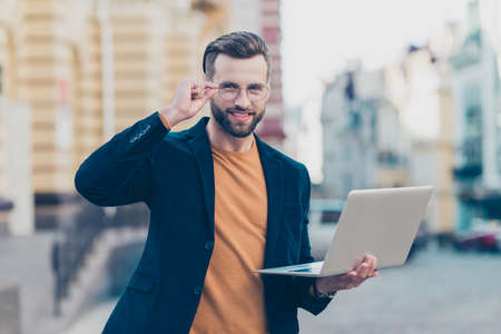 Portrait of cheerful glad gentleman holding eyelet of glasses on face having open laptop in hand looking at camera isolated on blurred background Stock Photo