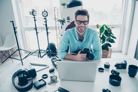 Portrait of cheerful positive man in shirt with modern hairstyle, sitting at desk, holding digital camera, looking at camera. Electronic devices computer laptop equipments concept Archivio Fotografico