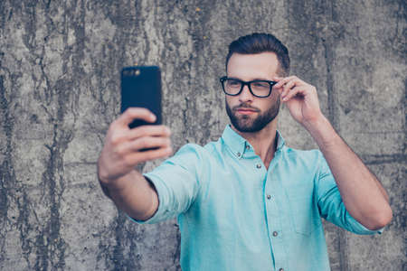 Portrait of harsh brutal man holding eyelet of glasses on face with dreamy expression shooting selfie on front camera of smart phone isolated on grey stone wall outside. Apps electronic device concept
