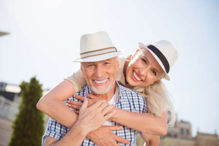 Portrait of cheerful positive couple with beaming smiles in straw hats, attractive man carrying on back charming woman, enjoying time together outdside Stock Photo
