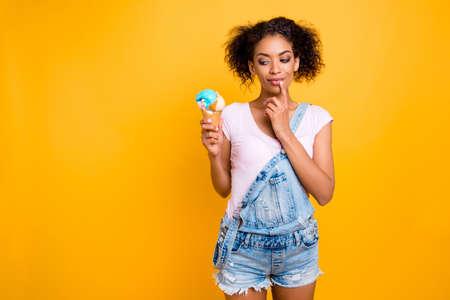 Portret met kopie ruimte van foxy dromerig meisje in spijkerbroek totaal kijken naar ijs in wafel kegel met vinger op kin geïsoleerd op gele achtergrond. Gewichtsverlies gezonde levensstijl concept