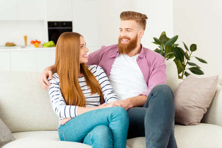 Portrait of two funny funky excited cute romantic lovely sweet gentle charming caucasian attractive adorable with toothy smile wife and husband resting in living room sitting on beige modern divan
