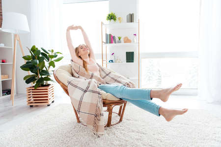 Portrait of positive cheerful girl sitting on cane armchair in comfortable apartment covered by plaid making stretching with close eyes enjoying domestic atmosphere