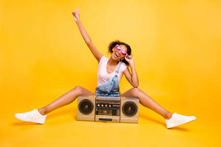 Portrait of fancy crazy girl in eyewear sneakers gesturing v-sign having boom box with cassette tape enjoying stereo sound. Party time music lover fan concept Stockfoto