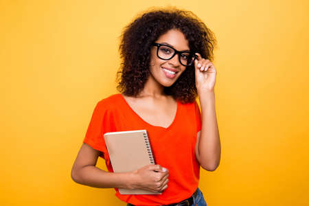 Portrait of trendy positive girl in eyewear holding eyelet of glasses on face holding notepad in hand going for lesson isolated on yellow background