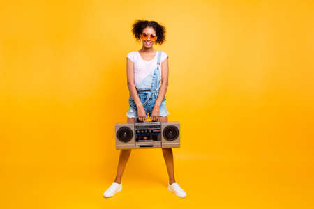 Full size portrait of fancy pretty girl in jeans jumpsuit sneakers eyewear holding boom box with cassette tape in hands looking at camera isolated on yellow background Stock Photo