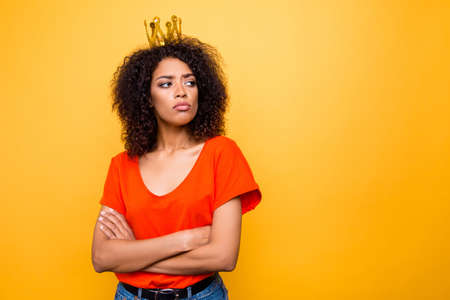 Portrait with copy-space empty place for advertisement of proud arrogant woman with modern hairdo holding arms crossed looking at empty place with offensive expression isolated on yellow background Stock Photo