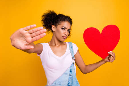 Portrait of sad serious girl gesturing palm stop sign holding big paper carton heart figure in hand isolated on yellow background. Disbelief distrust concept