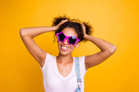 Portrait of cool fancy girl making two tails on head with hands having white beaming smile and plump lips wearing star glasses isolated on yellow background Stock Photo