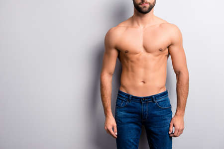 Cropped close up photo of handsome attractive ideal perfect stunning strong muscular flawless mans body with six-pack wearing dark blue denim jeans isolated on gray background copy-space