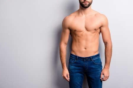Ritagliata da vicino la foto del corpo dell'uomo impeccabile muscolare forte, perfetto, perfetto, attraente, attraente, perfetto, con, confezione da sei, indossare jeans denim blu scuro, isolato su sfondo grigio, copia-spazio