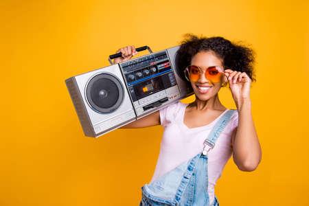 Porträt des ausgefallenen zahnigen Mädchens mit strahlendem Lächeln in der Brille, die Boombox auf Schulter betrachtet, die Kamera lokalisiert auf gelbem Hintergrund betrachtet. Musikliebhaber Fan Hobby-Konzept Standard-Bild