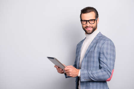 Portrait with copy space, advertisement concept,  virile, attractive, stunning man in glasses having  tablet in hands, looking at camera, standing over gray background