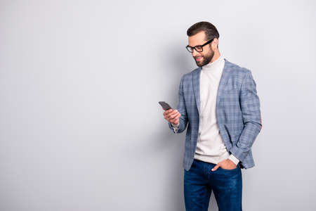 Harsh, virile, modern, attractive man with bristle, hairstyle in jacket and turtleneck  using 3G internet, holding smart phone, hand in pocket, reading sms, email over gray background with copy space