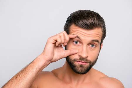 Gespierde, mannelijke, vermoeide man opent zijn oog wijd met vingers, met roodheid van binnen vanwege slaapgebrek, toont zijn probleem aan oogarts, geïsoleerd over grijze achtergrond