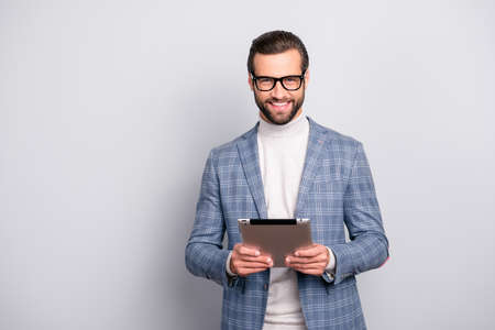 Portrait of  virile, attractive, stunning man in glasses using, having tablet in hands, looking at camera, standing over gray background Stok Fotoğraf - 106230915