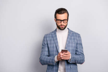 Harsh, concentrated, virile, intelligent man with bristle, hairstyle in checkered jacket using wifi, 5G internet on smart phone, checking email, typing sms, browsing over gray background