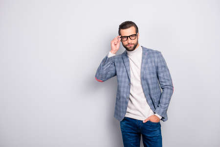 Portrait of handsome serious attractive confident elegant with modern haircut wearing classic checkered gray jacket keeping hand in pocket isolated on gray background copyspace Stock fotó