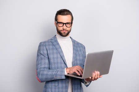 Portrait of  virile, attractive, stunning man in glasses using, having laptop in hands, looking at camera, standing over gray background