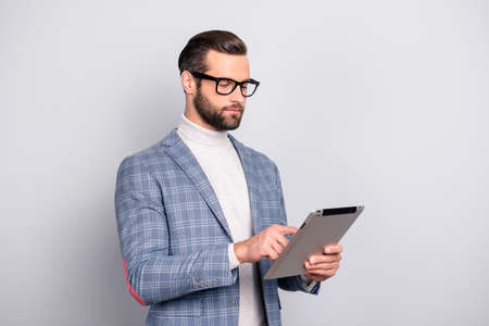 Portrait of half turned, virile, attractive, stunning man in glasses having  tablet in hands, checking email, using wi-fi internet, standing over gray background