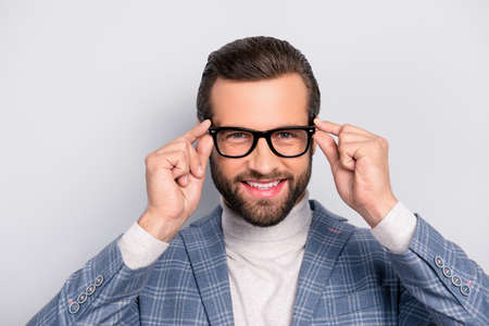 Portrait of gentlemen, manly, stunning,  modern man with hairstyle holding two eyelets of glasses on his face with fingers, looking at camera over gray background Stok Fotoğraf