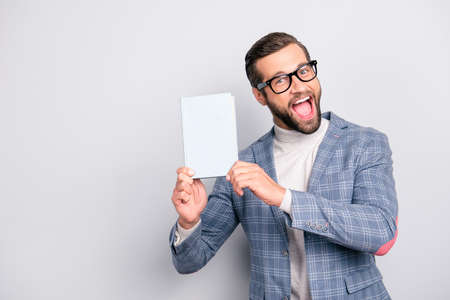 Gentlemen, attractive, clever, manly, stunning, crazy man geasuring, book  looking at camera with wide open mouth over gray background Stok Fotoğraf - 105622711