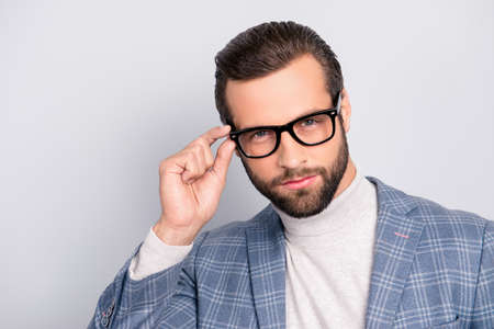 Portrait of gentlemen, manly, stunning, dreamy, inteligent man holding eyelet of glasses on his face with fingers, looking at camera over gray background Stok Fotoğraf - 105622713